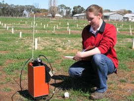 Woman using scientific equipment in a paddock